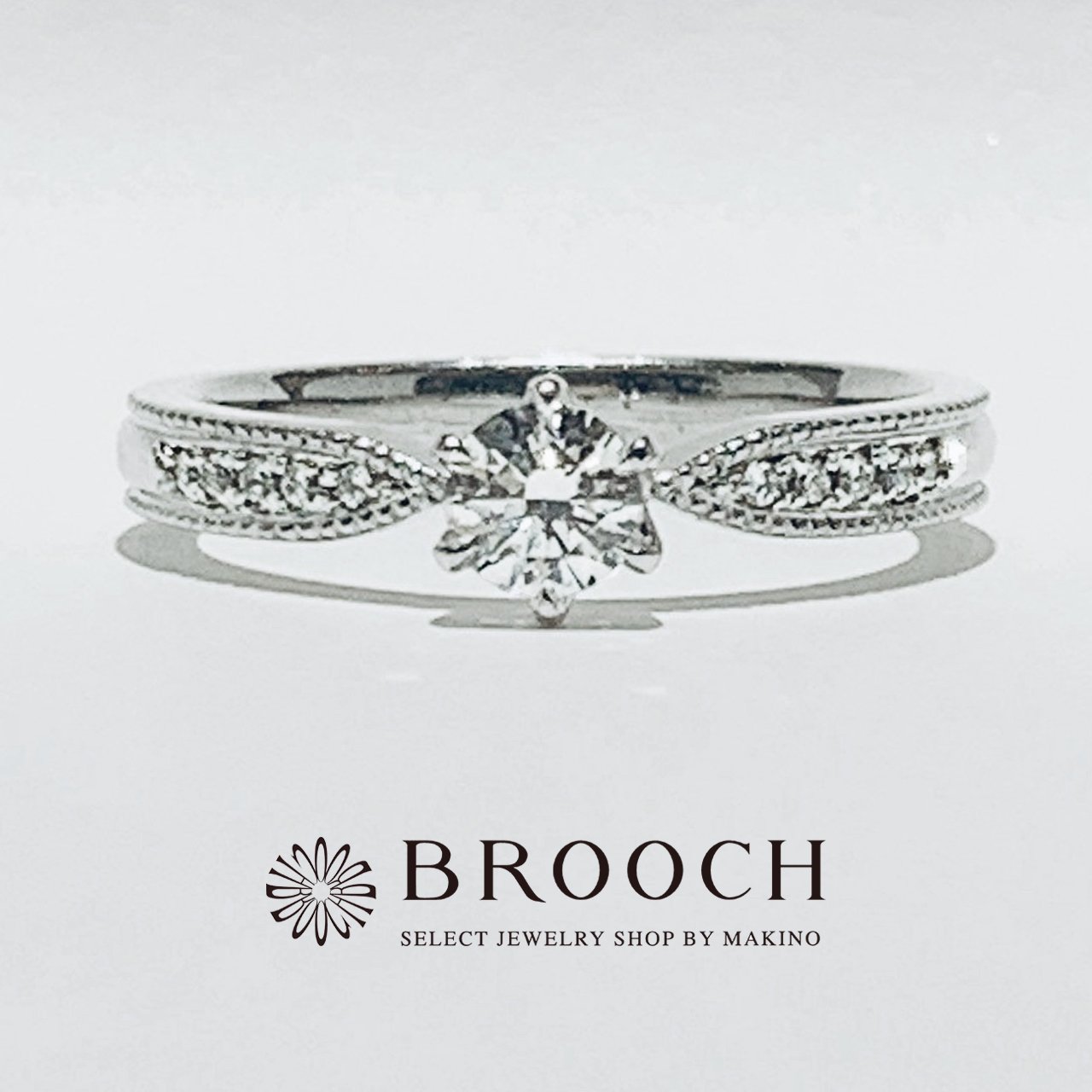 BROOCH 婚約指輪 エンゲージリング かわいい 両サイドメレ ミル打ちデザイン